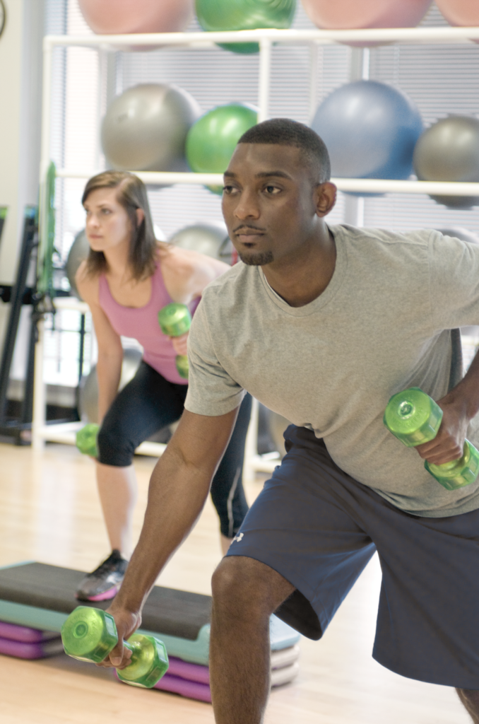 two people lifting weights in a workout class