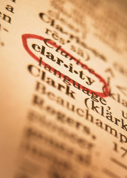 """Photo of a close-up shot of a dictionary page, at an angle.  The word """"clar-i-ty"""" is circled in red ink."""