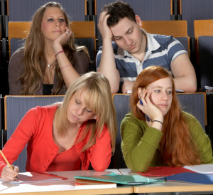 Photo of four students sitting in a classroom, all in postures of boredom.