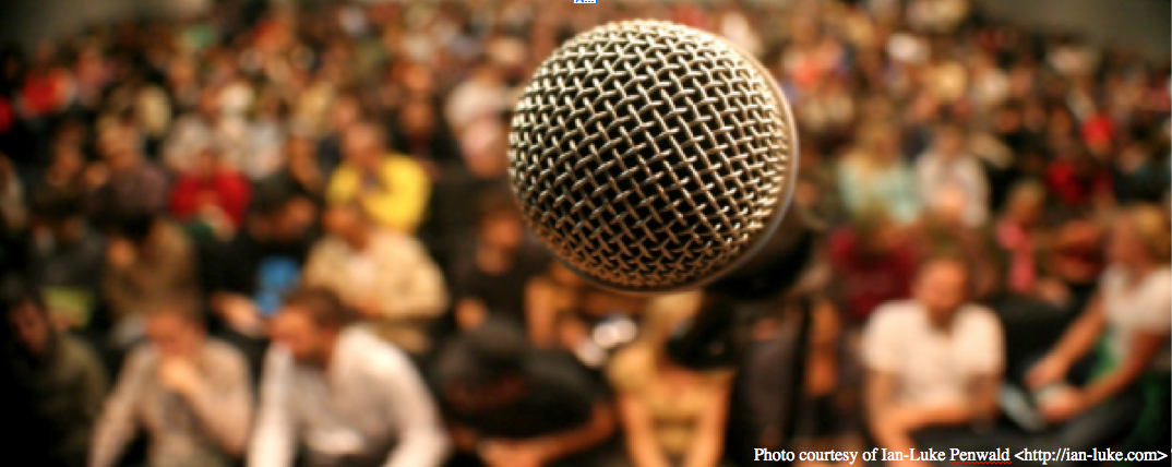 Photo of a microphone, close-up, with a large audience in the blurry background