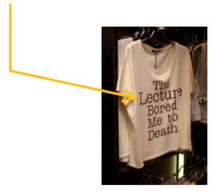 """Photo of a rack of white T-shirts  that say """"The Lecture Bored Me to Death.""""  Extending from the photo is a thin yellow line, with an arrow to the message on the shirt."""