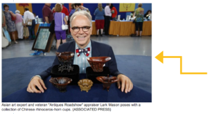 Photo of a commentator from Antiques Roadshow, sitting at a table, wearing a bow tie, suit, and dark glasses, smiling.